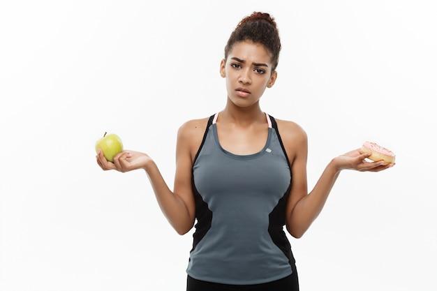 Gesundes und diätkonzept - schöner sportlicher afroamerikaner treffen eine entscheidung zwischen donut und grünem apfel. getrennt auf weißem hintergrund.