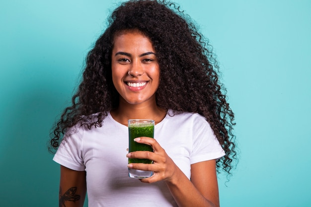 Gesundes und fitness-konzept - schöne amerikanische afrikanische dame im fitness-stoff, der gesundes gemüsegetränk trinkt.