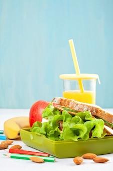 Gesundes und frisches sandwich, apfel und orangensaft für studentenmittagessen