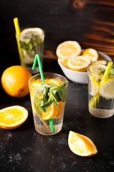 Gesundes und köstliches detox-wasser aus zitronen und orangen neben geschnittenen früchten auf dunklem vintage-holzhintergrund