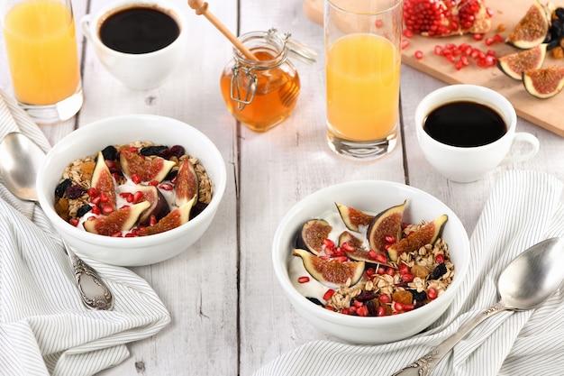 Gesundes und leckeres frühstück. haferflockenmüsli mit griechischem joghurt, frischen feigen, getrockneten früchten und granatapfel.