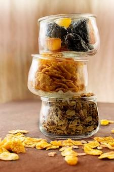 Gesundes und leckeres frühstücksgranola, cornflakes und trockenfrüchte in gläsern. vegetarier und veganer. hochkant. copyspace.