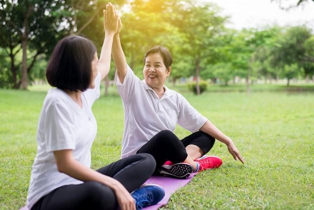 Gesundes und lifestyle-konzept, asiatische frauen heben die hände und entspannen sich am morgen im park zusammen, glücklich und lächelnd, positives denken