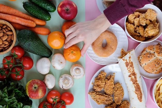 Gesundes und ungesundes schnellimbiß auf rosa und grün