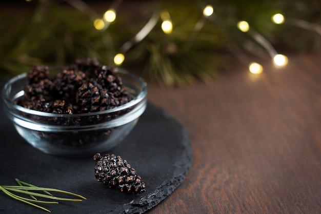 Gesundes veganes dessert von getrockneten tannenzapfen serviert in glasschale auf dunkelbraunem holztisch