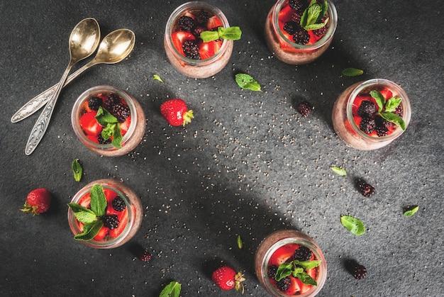 Gesundes veganes frühstück. dessert. alternatives essen. pudding mit chiasamen, frischen erdbeeren, brombeeren und minze. . ansicht von oben