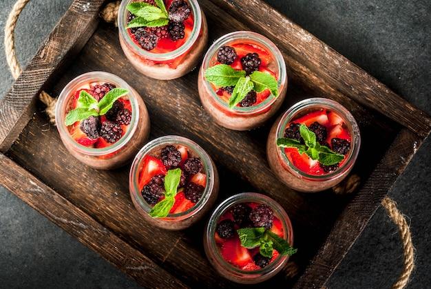 Gesundes veganes frühstück. dessert. alternatives essen. pudding mit chiasamen, frischen erdbeeren, brombeeren und minze. auf einem dunklen steinhintergrund in einem alten hölzernen behälter. ansicht von oben