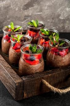 Gesundes veganes frühstück. dessert. alternatives essen. pudding mit chiasamen, frischen erdbeeren, brombeeren und minze. auf einem dunklen steinhintergrund in einem alten hölzernen behälter. copyspace