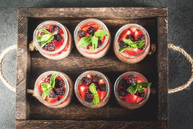 Gesundes veganes frühstück. dessert. alternatives essen. pudding mit chiasamen, frischen erdbeeren, brombeeren und minze. in einem alten holztablett. ansicht von oben