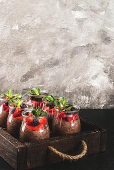 Gesundes veganes frühstück. dessert. alternatives essen. pudding mit chiasamen, frischen erdbeeren, brombeeren und minze. in einem alten holztablett.