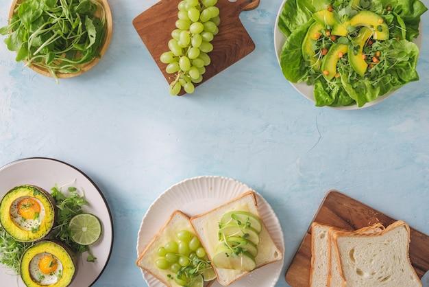 Gesundes veganes frühstück. diät. gebackene avocado mit ei und frischem salat aus rucola, toast und butter. auf einer weißen marmorplatte ein heller betontisch. eine tasse kaffee. platz kopieren