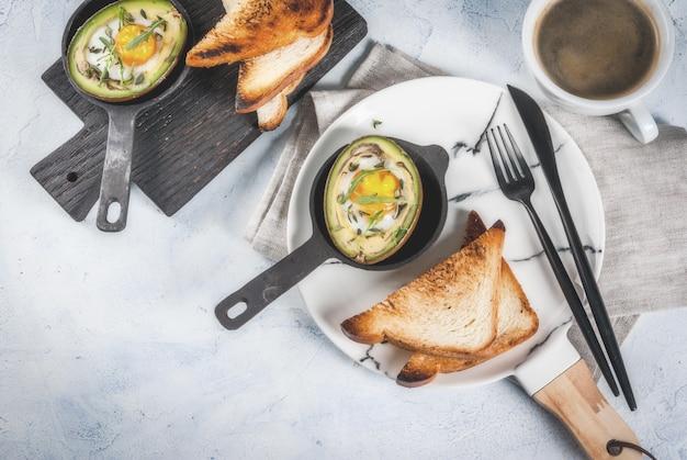 Gesundes veganes frühstück diät gebackene avocado mit ei und frischem salat aus rucola toast und butter auf einer weißen marmorplatte eine leichte konkrete tabelle