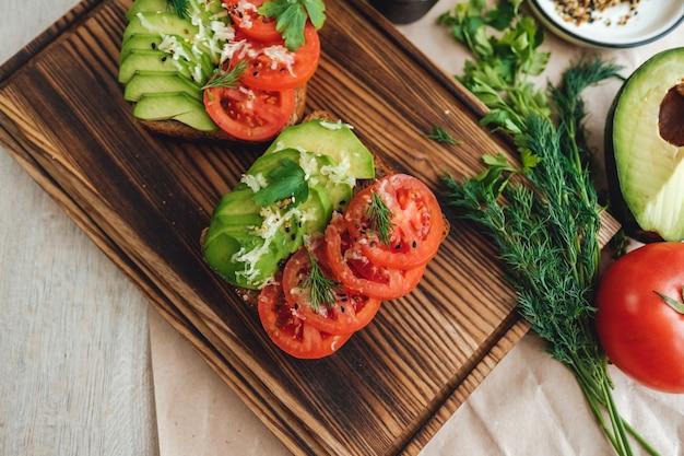 Gesundes veganes hausgemachtes sandwich, avocado und tomaten mit dunklem kornbrot auf einem holzbrett.
