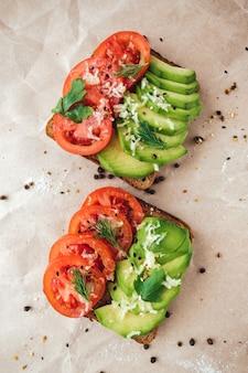 Gesundes veganes hausgemachtes sandwich, avocado und tomaten mit dunklem kornbrot auf papierhintergrund.