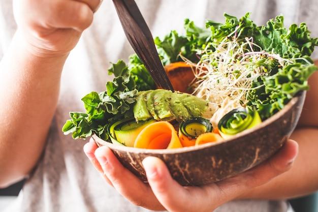 Gesundes veganes mittagessen in einer kokosnussschale. ein kind, das buddha-schüssel isst.
