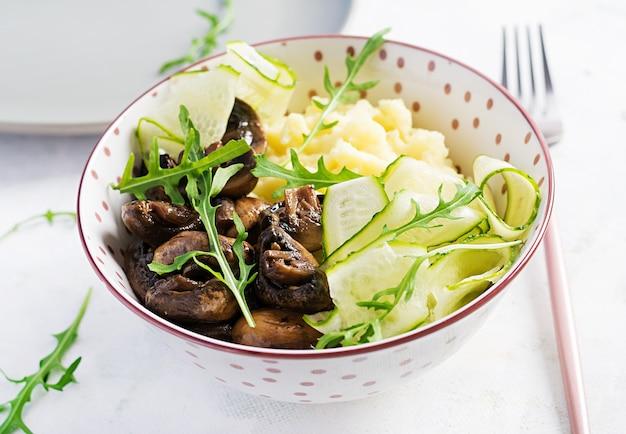 Gesundes veganes mittagessen mit kartoffelpüree und gebratenen champignons mit frischer gurke