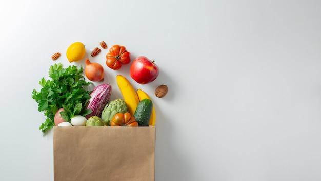 Gesundes veganes vegetarisches essen in papiertüte gemüse und obst auf weiß