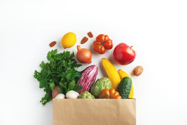 Gesundes veganes vegetarisches essen in papiertütengemüse und -obst auf weiß, kopienraum. einkaufen lebensmittelsupermarkt und sauberes veganes esskonzept.