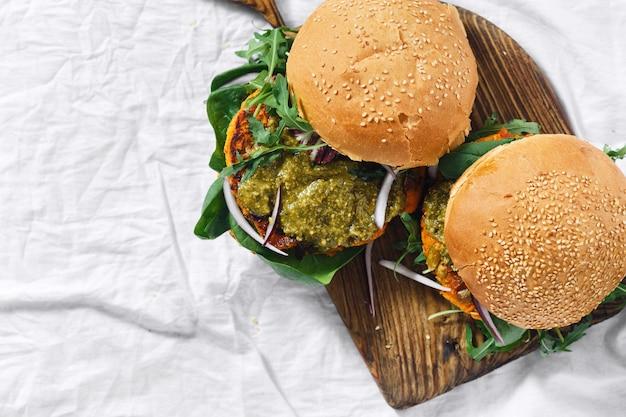 Gesundes vegetarisches draufsicht copyspace hölzernen brettes lebensmittelburger-kürbisspinat arugula pesto