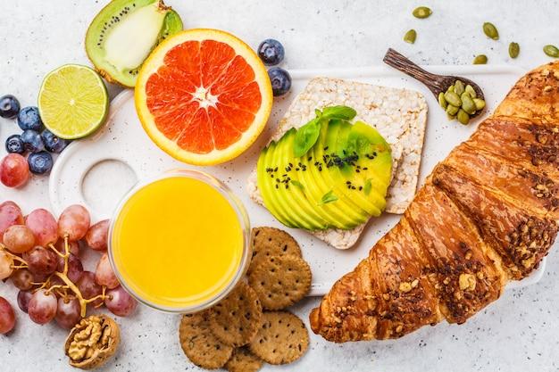 Gesundes vegetarisches frühstück mit hörnchen, avocadotoast, frucht und saft auf einer weißen platte.