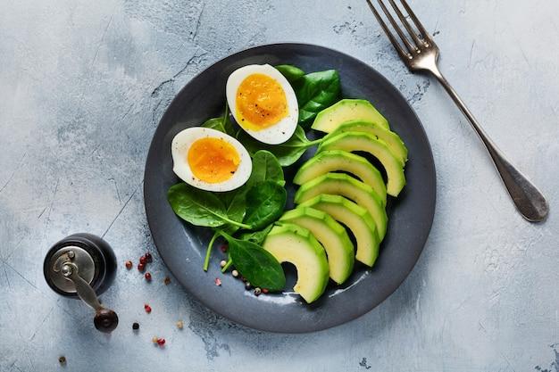 Gesundes vegetarisches salatfrühstück. spinatblätter, tomaten, avocado und gekochtes ei auf grauem teller und grauem beton alt