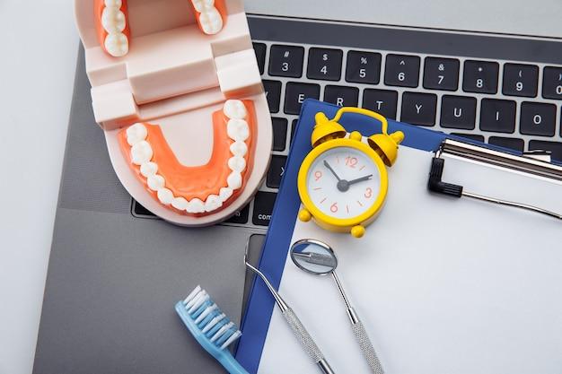 Gesundes zahnmodell mit zahnärztlichem werkzeug und wecker in der zahnarztpraxis. professionelles zahnhygienekonzept