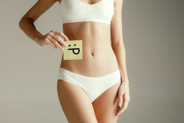 Gesundheit der frau. weibliches modell, das karte mit emoji nahe magen hält junges erwachsenes mädchen mit papier für zeichen oder symbol lokalisiert auf grauer wand. körperteil ausschneiden. medizinisches problem und lösung.