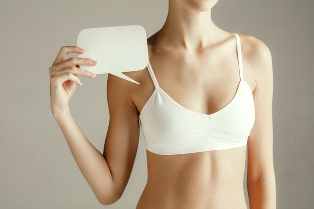 Gesundheit der frau. weibliches modell, das leere karte nahe brust hält. junges erwachsenes mädchen mit papier für zeichen oder symbol lokalisiert auf grauem studiohintergrund. körperteil ausschneiden. medizinisches problem und lösung.