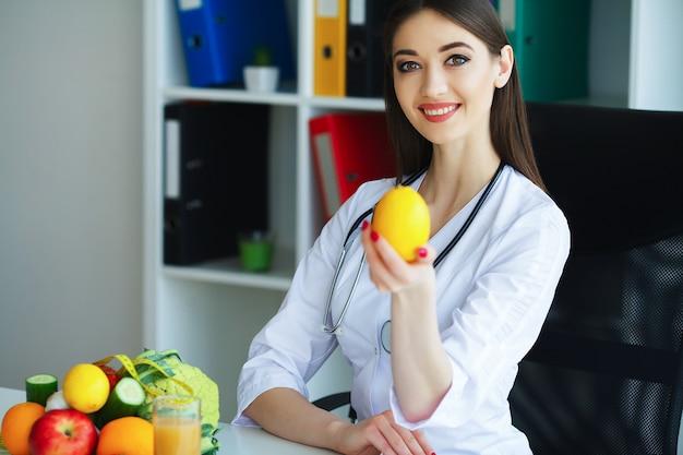 Gesundheit. doktor dietitian smiles und shows lemon. frau hält obst in händen. junger doktor mit einem schönen lächeln im hellen büro.