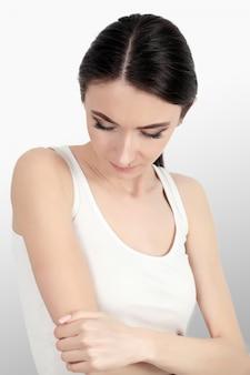Gesundheit. frau in den schmerz, die schlecht und krank sich fühlen, kopfschmerzen und fieber habend und halten hand. schönes unglückliches müdes mädchen, das unter schmerzlichem hauptschmerz und druck leidet. gesundheitswesen.