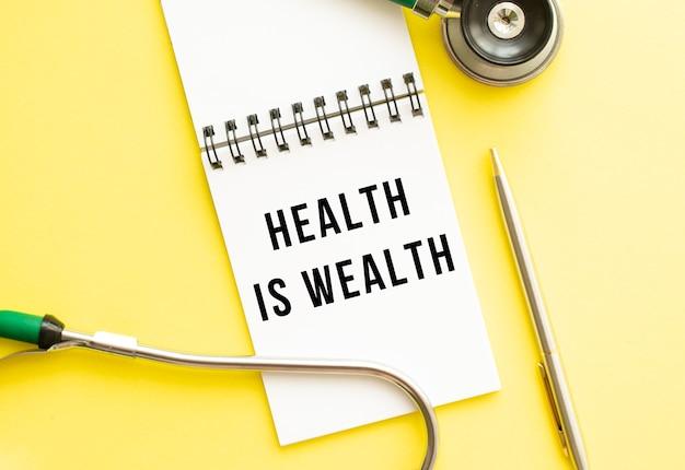 Gesundheit ist gesundheit steht in einem notizbuch auf einer farbtabelle neben stift und stethoskop. medizinisches konzept