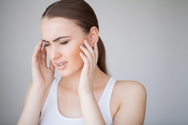 Gesundheit und kopfschmerzen. schöne frau, die die starken kopfschmerzen, schmerz fühlend hat