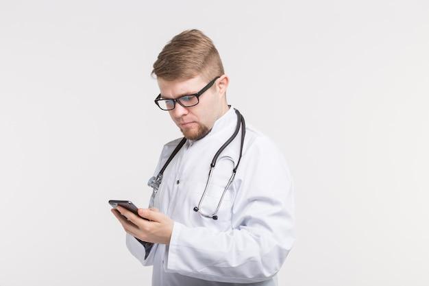 Gesundheit und medizin - arzt trägt das stethoskop und schaut auf den bildschirm des telefons auf weißem hintergrund.