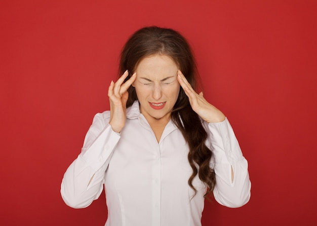 Gesundheit und schmerz. gestresste erschöpfte junge frau, die starken spannungskopfschmerz hat.