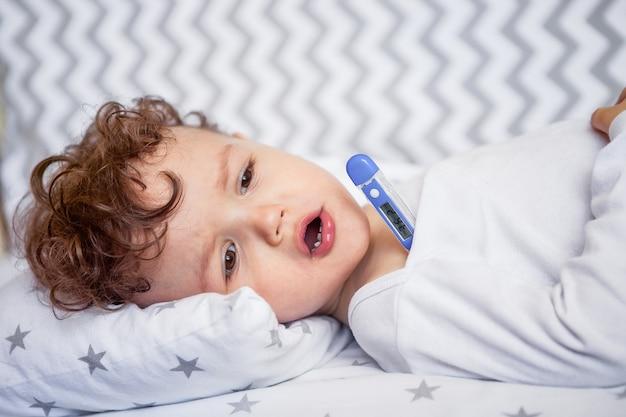 Gesundheit von kindern. ein kind mit einem thermometer in seinen händen zu studieren. zunge herausstrecken, interesse an medizin