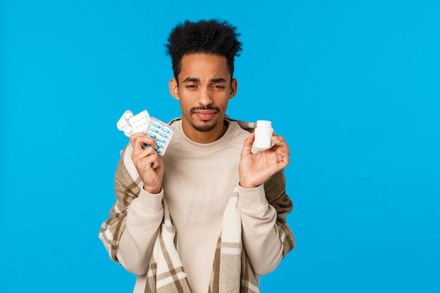 Gesundheits-, medikations- und wintersaisonkonzept. der junge afroamerikanerkerl, der drogen und eine flasche pillen hält und niest, fühlen sich unwohl müdigkeit von der grippe, die erkältung und stehen in der umfassenden blauen wand