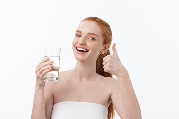 Gesundheits-, menschen-, lebensmittel-, sport-, lifestyle- und beauty-inhalte - lächelnde junge frau mit einem glas wasser.