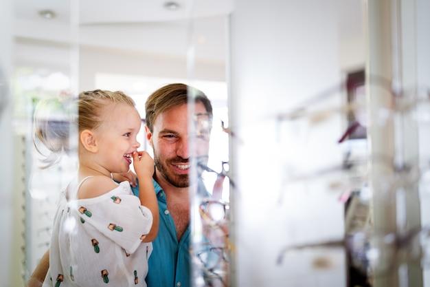 Gesundheits-, seh- und sehkonzept. glückliches kind, das mit ihrem vater im optikgeschäft eine brille auswählt