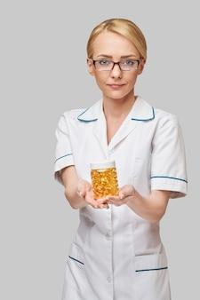 Gesundheits- und diätkonzept - ernährungsberater oder kardiologe, der fischöl in kapseln für vitamin d und omega-3-fettsäuren hält