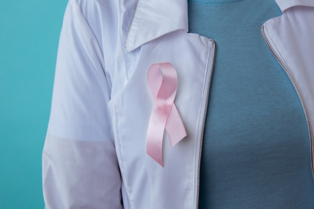 Gesundheits- und medizinkonzept - frau im leeren t-shirt mit rosa brustkrebs-bewusstseinsband