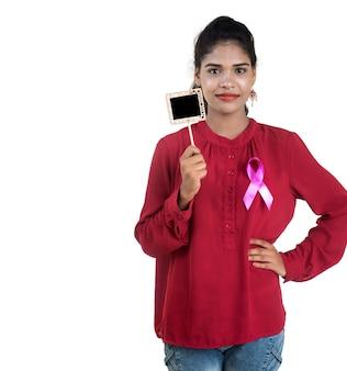 Gesundheits- und medizinkonzept - junge frauenhände, die rosa brustkrebs-bewusstseinsband und kleine tafel halten