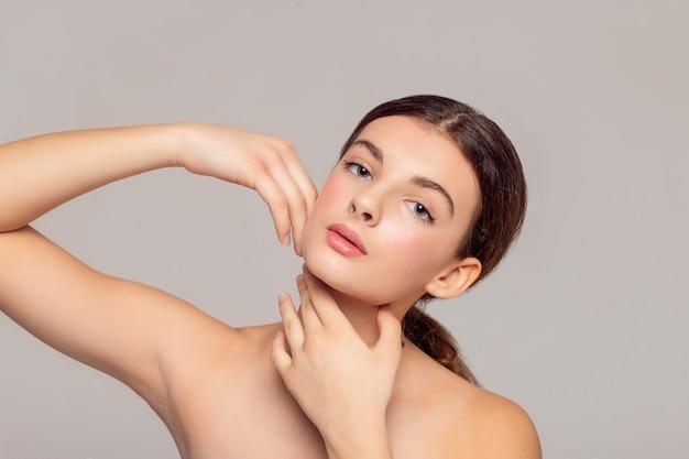 Gesundheits- und schönheitskonzept - schöne junge frau mit sauberer frischer haut berührt eigenes gesicht. gesichtsbehandlung . kosmetik, beauty und spa.