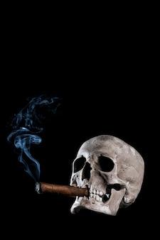 Gesundheitsgefahrenkonzept, nahes hohes porträt der vertikale schädel mit einer zigarre und einem rauche