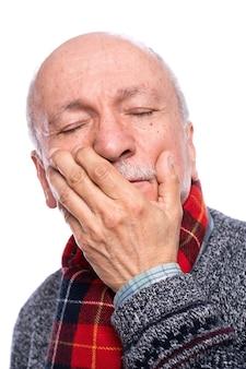 Gesundheitskonzept. älterer mann, der unter kopfschmerzen über weißem hintergrund leidet