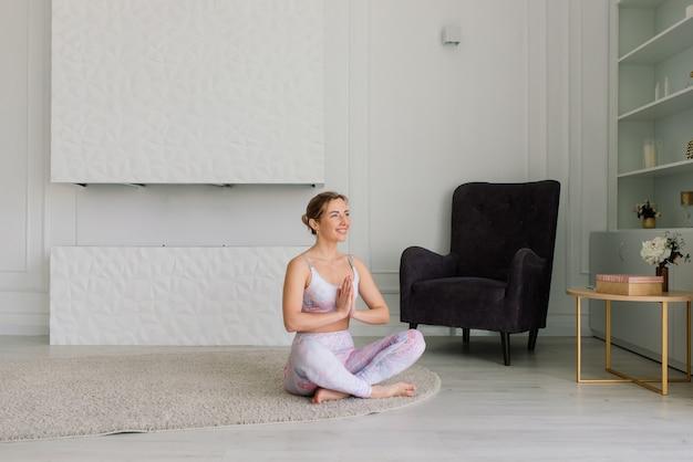 Gesundheitskonzept. junge schöne frau macht yoga-übungen im modernen raum