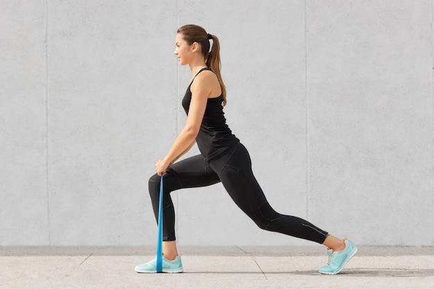 Gesundheitskonzept. schöne frau mit gesunder haut, pferdeschwanz, hat übungen mit gummiband, gekleidet in sportkleidung