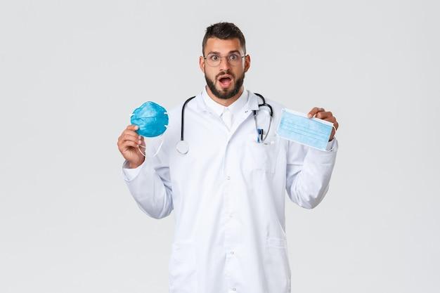 Gesundheitspersonal, krankenversicherung, pandemie und covid-19-konzept. aufgeregter männlicher arzt in brille und weißem kittel, arzt mit medizinischer maske und beatmungsgerät, erstaunt keuchend