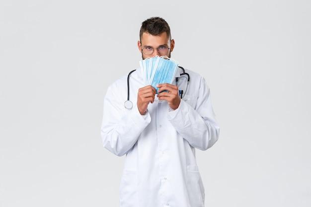 Gesundheitspersonal, krankenversicherung, pandemie und covid-19-konzept. lustiger gutaussehender arzt, hispanischer arzt in weißem kittel und brille, der medizinische masken zeigt, verwendet ihn während des coronavirus