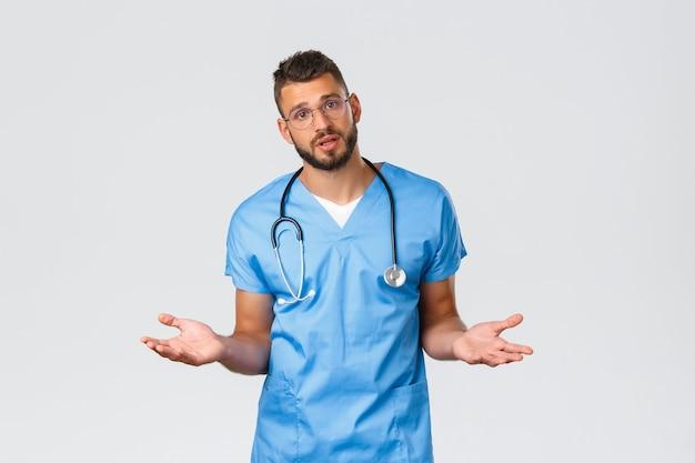 Gesundheitspersonal, medizin, covid-19 und pandemisches selbstquarantänekonzept. entschlossener junger berufsarzt, arzt in der notaufnahme mit peeling, hände seitlich ausbreiten, rezept erklären