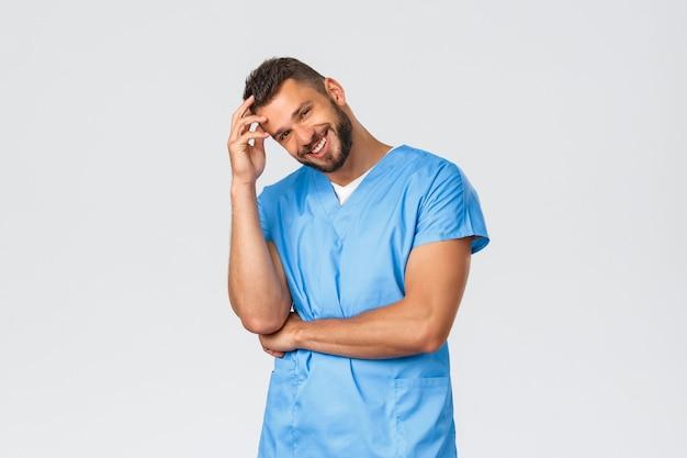 Gesundheitspersonal, medizin, covid-19 und pandemisches selbstquarantänekonzept. hübscher hispanischer krankenpfleger, arzt in blau scheuert lächelnde kamera, kümmert sich um patienten in der klinik.